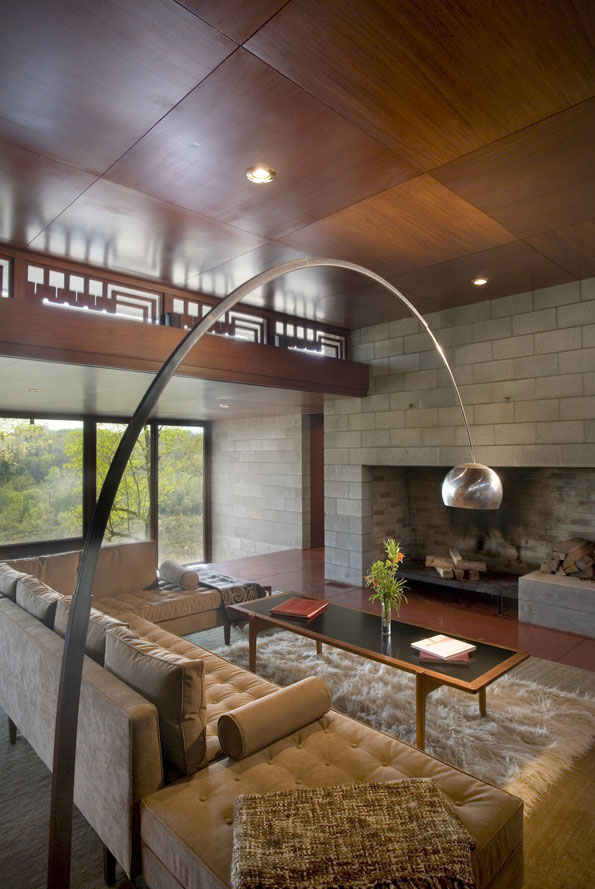 "An iconic Arco floor lamp soars over the central living space toward a stone fireplace. Wright often described fireplaces as ""the heart and soul of a house."""