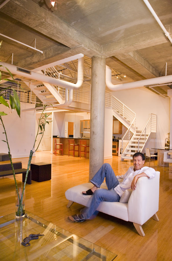 Julian Epstein relaxes on a modern chaise longue in the open living space of his PN Hoffman-built loft.