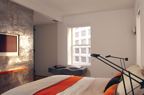 The master bedroom, with its unique aluminum wall which envelops the television. The bedding, by Aero, is available at Apartment Zero.