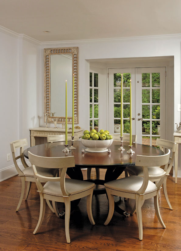 The smaller dining room is simply furnished in ivory-painted Klismos chairs, designed by Randolph, pulled up to a custom-made round maho