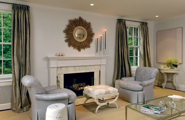 In the living room, pale armchairs, an ottoman and silk drapes reflect designer Frank Babb Randolph's signature style. Randolph found the vintage starburst mirror over the reconfigured fireplace mantel in a Boston antique shop.