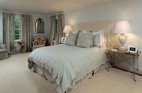 The master bedroom is furnished simply in a custom-designed headboard and nickel-plated bedside tables set with lamps made from antique Italian porcelain vases.