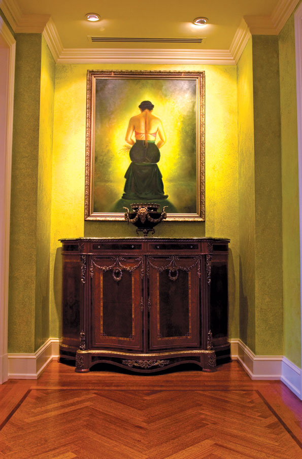 The entry hall of William and Janet Cohen's Chevy Chase penthouse features an oil painting of a young Vietnamese woman alongside an ornate French Empire style cabinet.