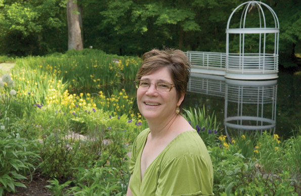 Kara Kibler (above) stands near a gazebo beside a pond connected to the garden by Yellow Flag Iris (Iris pseudacorus) and other water-friendly plants.