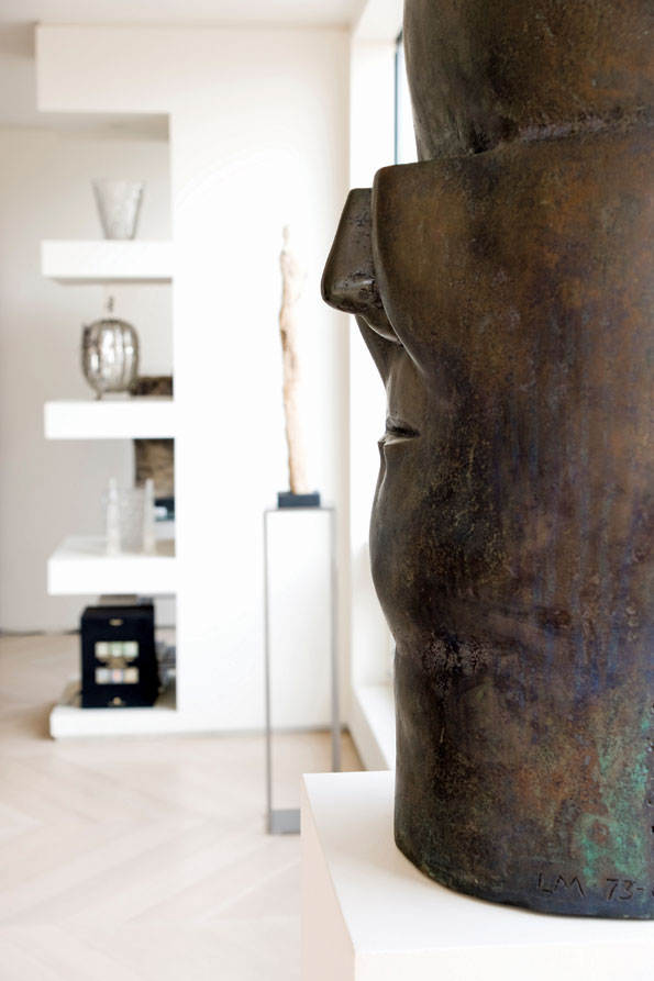 A large scale, massive bronze sculpture by Chilean artist Luis Madiola (foreground) is juxtaposed against the floating display shelves in the background.