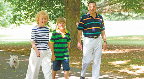 Ambassador of the Russian Federation Yuri Uskahov, his wife Svetlana, and grandson Misha, followed by dog Simon, stroll the lushly planted grounds of the Eastern Shore dacha.