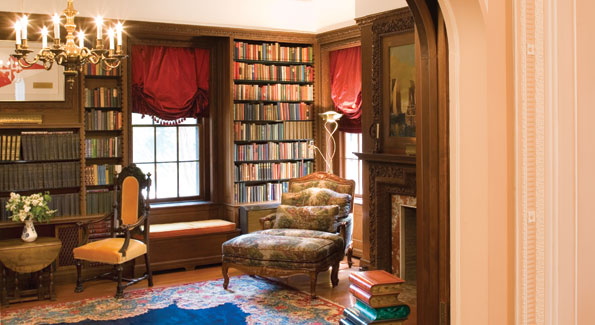 Off the living room, the walnut-paneled library incorporates built-in window seats and shelving holding books in Russian and English.  The oriental rug and tapestry-upholstered bergere are typical of the furnishings throughout the house.