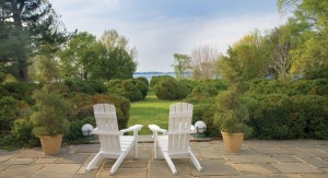 From the rear flagstone patio, a view of the Chester River beckons through clustered boxwoods.