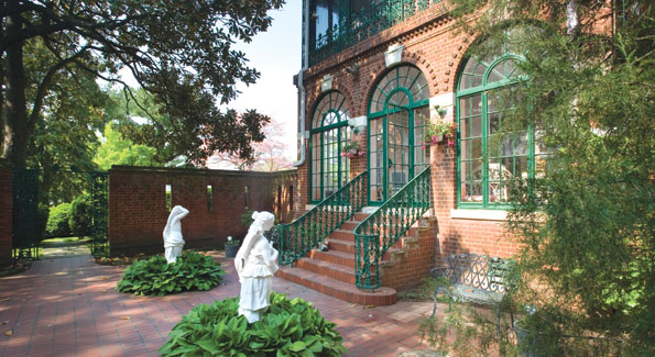 Wrought ironwork accents the brick facade fronting the side courtyard off the enclosed living room porch.