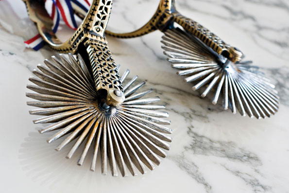 """Traditional Chilean sterling silver """"Huaso"""" (cowboy) spurs are tied with a silk bow representing the national colors of Peru."""