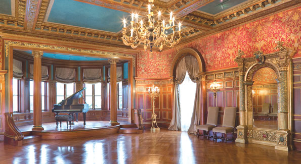 The ballroom was most likely designed around the antique 19th Century red silk tapestry based on 16th Century patterns. The ornate circular latticed doorway and the ornamented vaulted ceiling of gold leaf and turquoise carvings are as spectacular as the original parquet flooring. Pearl grey silk peau-de-soie curtains and matching ballroom chairs compliment the tapestry.