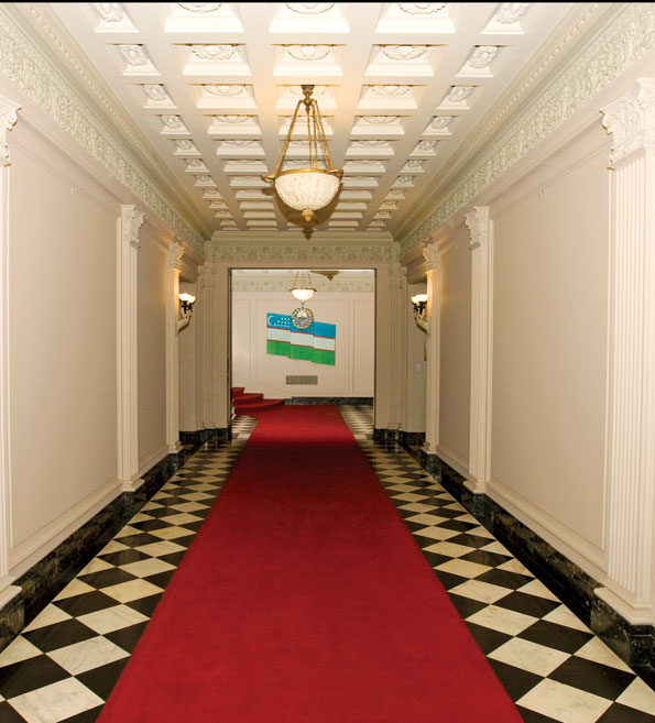 The expansive Entry Hall, which features fluted pilasters, an elaborate coffered ceiling, ornate carvings, and a checkerboard marble floor, connects to the grand staircase in the rear. The bas-relief flag of the Republic of Uzbekistan dominates the background