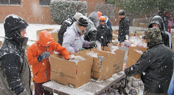 Volunteers brave a snowstorm to distribute produce, meat and other essentials to over 3,000 Alexandrians. (Photo by Jane Hess Collins)