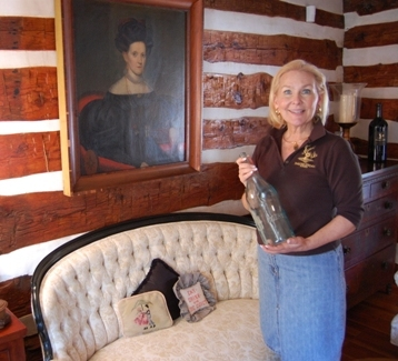 Winery founder Jane Kincheloe holds a vintage bottle from the 19th century days of the old Paradise Springs. Photo by John Arundel