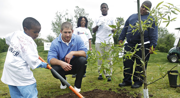 Chris Cooley helps plant a tree with the junior golfers from The First Tee