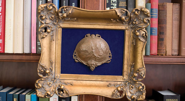 Nothing says study like a well-appointed library and framed artifacts, like this impressive bronze bas-relief hung mid-shelf