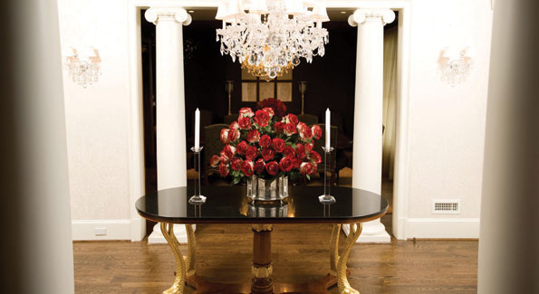 Despite ornate elements, the columns, crystal, and gilt carved table legs are perfectly proportioned to the foyer, which greets guests by hinting at the elegance to be found within