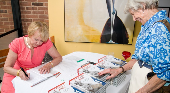 "Author Doreen Drewy Lehr signs a copy of her new release and first book, ""A Girl's War: A Childhood Lost in Britain's WWII Evacuation"" for fellow author Ann McLaughlin, whose sixth novel ""Leaving Bayberry House"" was just released."