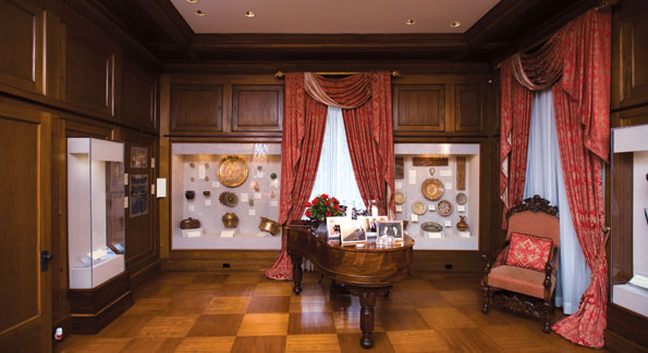 An antiquities collection surrounds a grand piano topped by family portraits. Photos by Joseph Allen.
