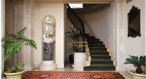 """Velvet handrails encase the graceful circular staircase. """"Nydia, The Blind Girl of Pompei"""" by Randolph Rogers greets guests in a special alcove. Photos by Joseph Allen."""