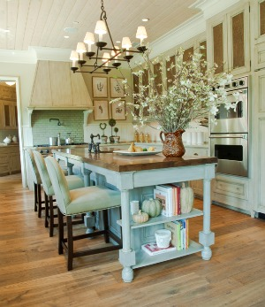 The designers used strie painted cabinets with antiqued caning inserts in the kitchen permitting a casual atmosphere taht is perfect for everyday entertaining. Photo by Marcos Galvany/Joseph Allen.