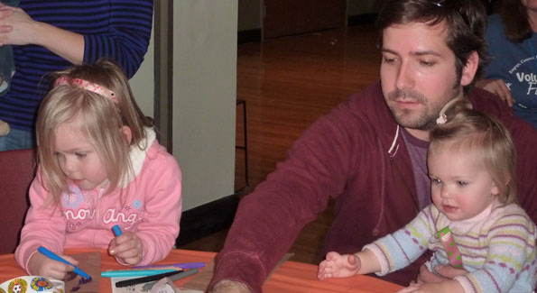 Chris Swenson and his daughters make crafts for needy children during last year's Give Together. Photo courtesy of Volunteer Fairfax.