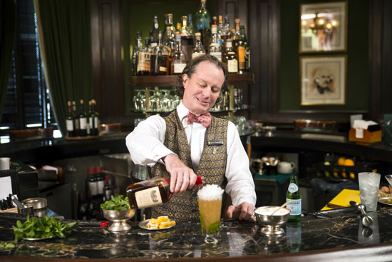 Hewes making the Round Robin's signature mint julep.