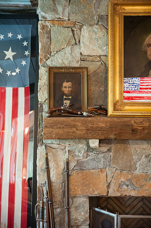 Detail of an Abraham Lincoln oil and antique rifles.
