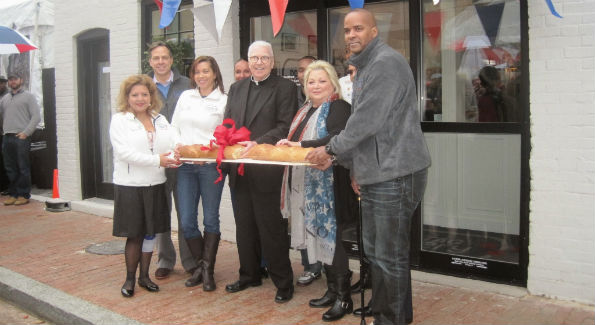 Why cut a ribbon when you can break bread? Guests gathered in front of the store to celebrate the official opening with the breaking of the bread and confetti. (Photo by Erica Moody)