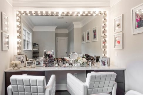 "The ""glam room"" on the second floor features white swivel chairs and a wall of mirrors."